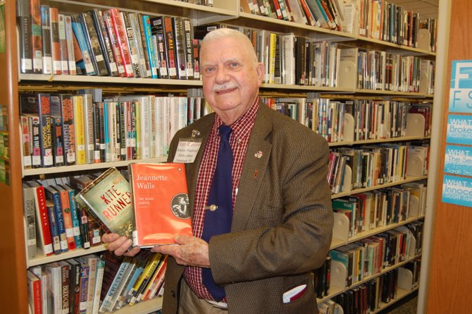 Stan Ransom, director of the Plattsburgh Public Library, stands in the library holding two of the titles that will be distributed for free on April 23.