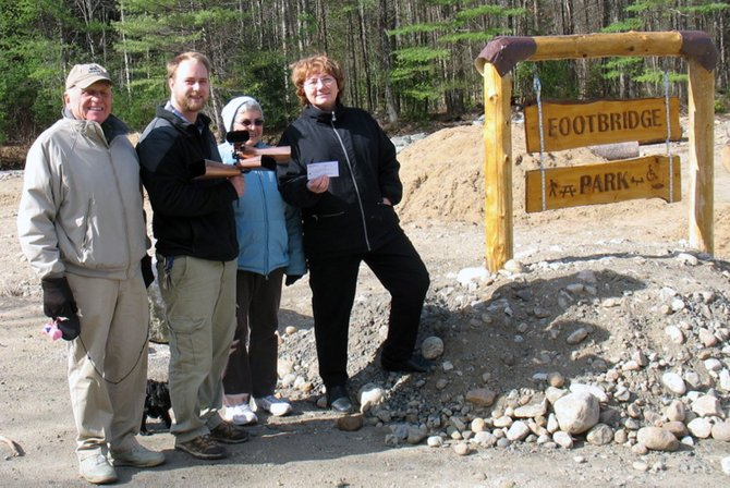 Elizabeth Bartley presents reward money to Nathaniel Galeraigh at Footbridge Park after he returned the park's missing cowbells, Rita and Gary Mitchell, who frequently enjoy walking through the Footbridge park, joined the group for the award.