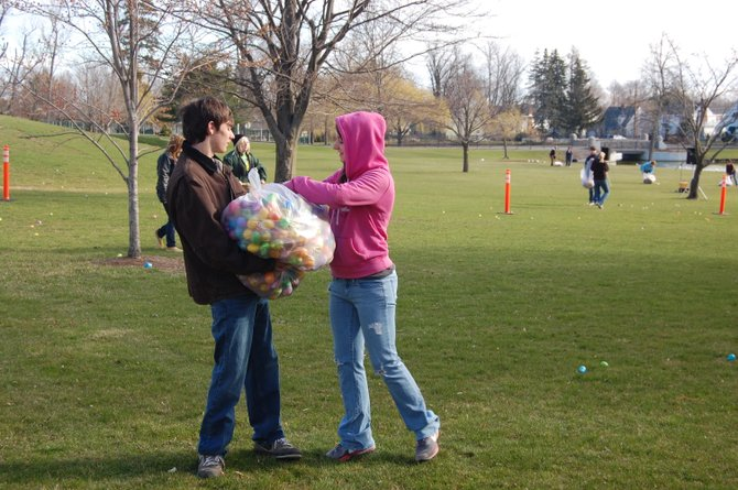 Alec Staley and Sierra Wimett, two students involved with the Upward Bound program, scatter Easter eggs for area children to find at CVPH Medical Center's annual Easter egg hunt.
