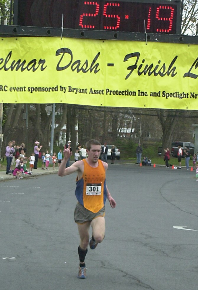 Clifton Park's Eric Macknight crosses the finish line as the men's division winner at Sunday's Delmar Dash.