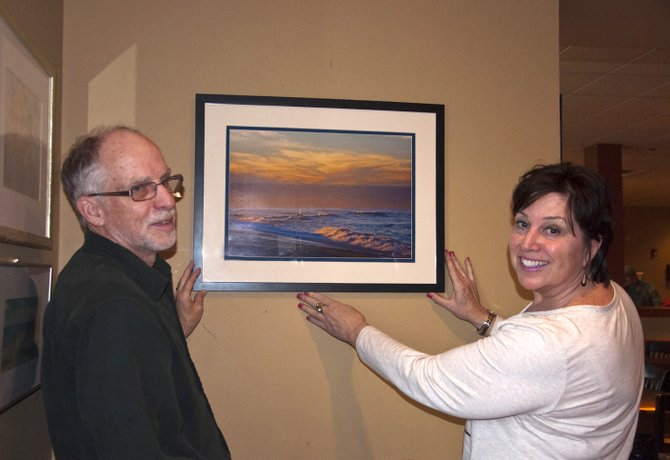 Cazenovia Arts members Chris Nevison, left, and Delynn Orton hang a new piece of local artwork on the wall at Dave's Diner on Sunday, April 15. Many of the pieces are available for purchase, and will remain in the restaurant for the next few months.
