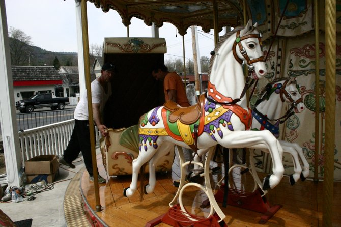 Workmen install a chariot coach on a carousel being erected this week near the southeast corner of Beach Road and Canada St. in downtown Lake George Village. The carousel, along with  its accompanying bumper-car attraction and bumper boat ride, is expected to be well-received by families seeking new activities in the resort village.