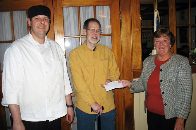 Matt Baldwin,  Deer's Head Chef and Mike Parker, Kiwanis President give Marilyn Jordan, Director of the Community Food Shelf a check for $1,000.