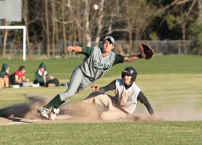 Crown Point's Nathan Tabor slides safely into third base as Chazy's Craig Botten makes a play during Mountain and Valley Athletic Conference baseball action April 18. Crown Point won, 8-2.