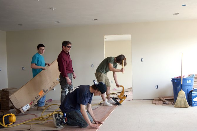 Students work on hardwood flooring in the home they built on Clemons Road.