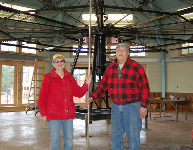 Adirondack Carousel Board co-organizers Marge and Ted Glowa show off the newly arrived carousel mechanics, which were delivered Monday, April 23 at the pavilion in William Morris Park, Saranac Lake. The carousel will open to the public on Saturday, May 26.