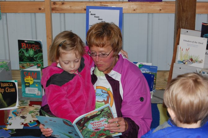 Pam Maloney reads a story to five-year-old Annabelle Johnson at an Earth Day event in Plattsburgh.