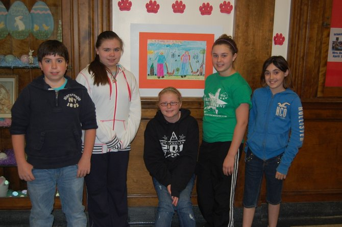 Mooers Elementary School fifth graders, from left to right, Jacob Steinfeld, Hannah Hemingway, Gabby Dumas, Olivia Gonyo and Faith Guerin, stand in front of one of the anti-bullying posters hanging throughout the school.