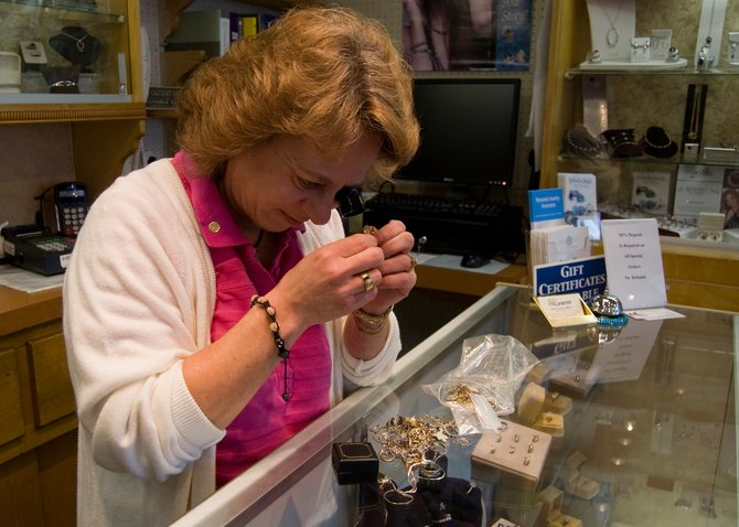 Sheryll Hoffman, owner of JM Jewelers on Mariaville Road in Rotterdam, inspects jewelry recently taken in on Tuesday, April 17. Hoffman would fall under a proposed new town law regulating secondhand dealers.