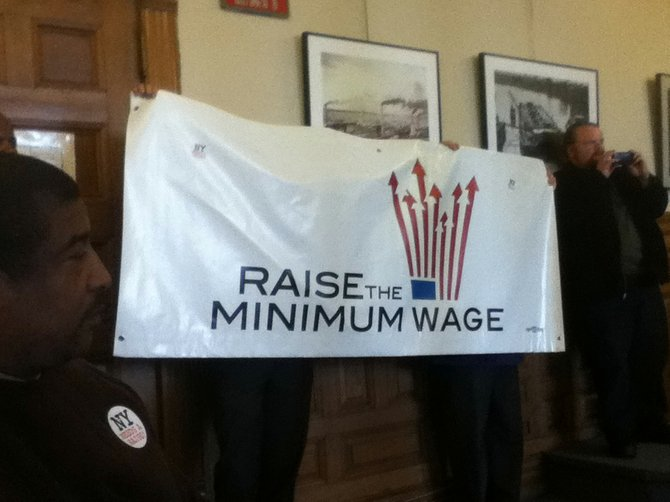 A group in favor of a minimum wage increase held this sign at a public forum last week in the Common Council Chambers.