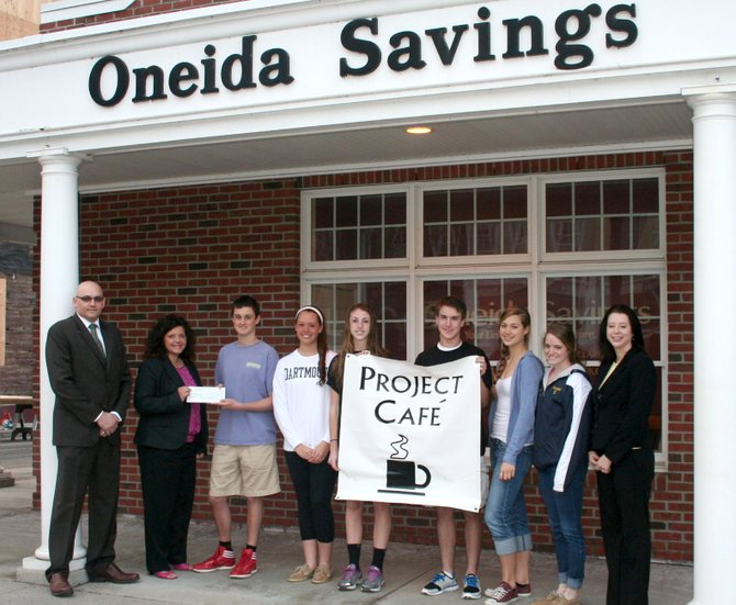 Project CAFÉ board member Victor Prial, left, stands alongside Barbara Houghton, AVP banking officer and regional lender at Oneida Savings Bank; Project CAFÉ students Matt Henderson, Sally Langan, Lucy Shephard, Sam Webster, Lila Seeley and Caroline Marshall; and Jennifer Bowden, office manager at Oneida Savings Bank after receiving a check for $3,000.