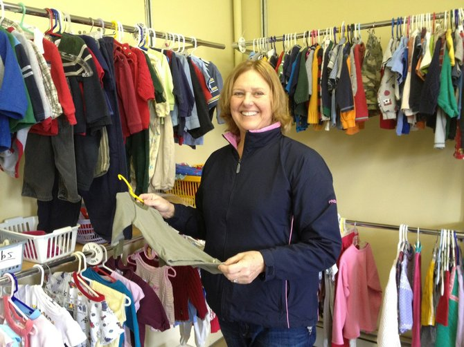 CazCares Client Services Director Gigi Redmond organizes clothing in the community closet, April 27. The local non-profit organization is celebrating 30 years of service this month.