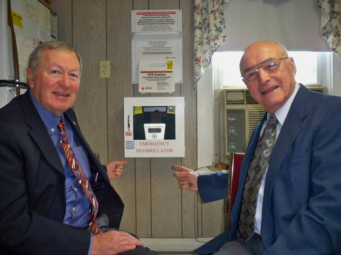 The Schroon Lake senior citizen club has purchased a Power Heart Automatic External Defibrillator (AED) to serve the community in case of a cardiac emergency. Looking at the equipment are Ed Donley, left, club first vice president, and Dick Newell, president.