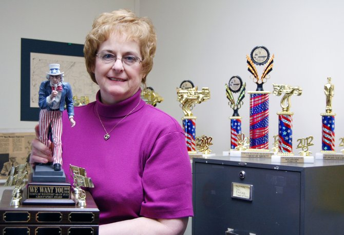 Sheila Borden holds the grand prize trophy for the upcoming Fourth of July parade float.