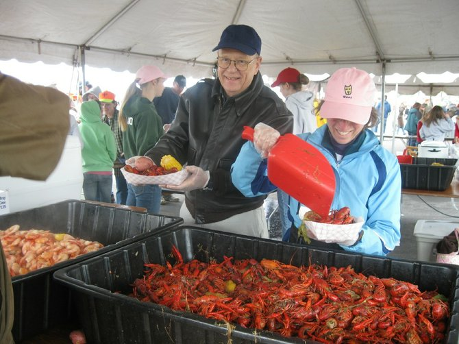 Serving crawfish at a past Crawfish Fest are Joe Kozelsky and Ellen Somers.