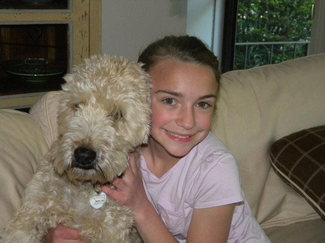 Olivia Grace Ralbovsky, winner of this year's DAR essay contest with her dog Louis, who is sometimes the subject of her writing. Photo Submitted.