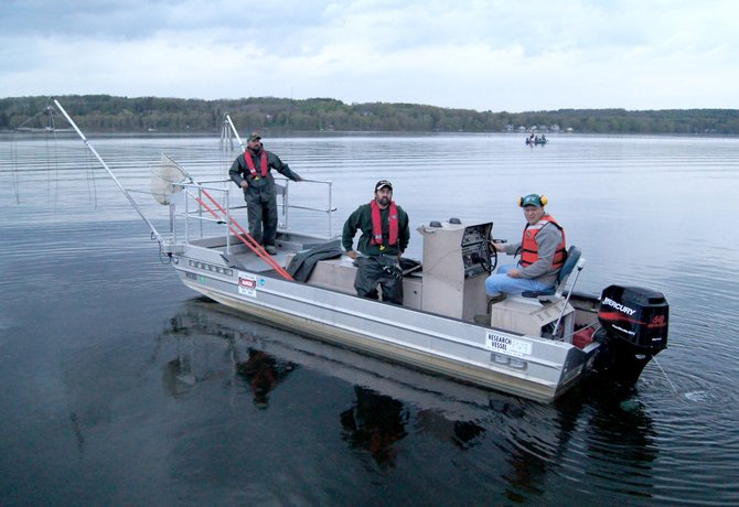 "ANCHORS UP: Fish and Wildlife Technician Ian Blackburn, left, and biologists Jim Everard and Scott Pringle prepare to survey Cazenovia Lake on May 9. The DEC representatives used ""electroshocking"" to subdue indigenous fish for observation and evaluation of water quality."