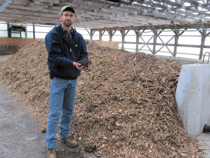 Plant operator Ryan Riefler, pictured inside the village of Marcellus Bio-solids Composting Facility, holds up freshly made compost. An open house is scheduled for 9 a.m. to noon Saturday, May 19.