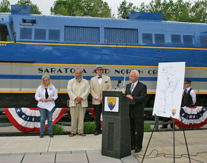 City of Saratoga Springs Mayor Scott Johnson (right) helps to launch the summer and fall 2012 season of the Saratoga & North Creek Railway at the Saratoga Springs Train Station on Wednesday, May 16. For the first time in its history, the railway will offer service seven days a week to its seven flag stops throughout the First Wilderness Corridor when the new season begins on Saturday, May 26. In celebration of the Memorial Day opening weekend, all active duty military and veterans will receive free round-trip and one-way rides from Saturday, May 26 through Monday, May 28. Additionally, passengers are encouraged to bring an item to donate to Operation Adopt-a-Soldier. Collection bins will be stationed at railway stops in Saratoga Springs and North Creek. From left to right: Operation Adopt-a-Soldier Co-Chair Terri Perry; Town of Johnsburg Supervisor Ron Vanselow; and Saratoga & North Creek General Manager Steve Torrico.