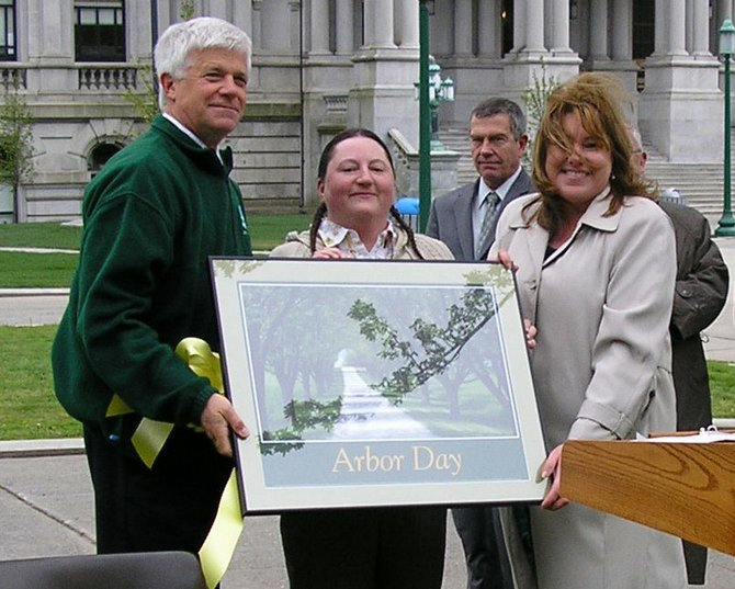 "At New York's Arbor Day ceremony held April 27 in Albany, Department of Environmental Commissioner Joseph Martens noted, ""Arbor Day is a national observance that celebrates the essential role trees play in our environment.""   A photo submitted by Ticonderoga photographer Tonya Whitford Condon, center, was selected by the State Arbor Day Committee to be featured on the official New York Arbor Day Poster.  Joining Condon and Martens was Mary Kramarchyk of the State Arbor Day Committee as the award winning poster was unveiled.  The poster is printed on paper made at International Paper's Ticonderoga mill from trees harvested in accordance with the principles of the Forest Stewardship Council."