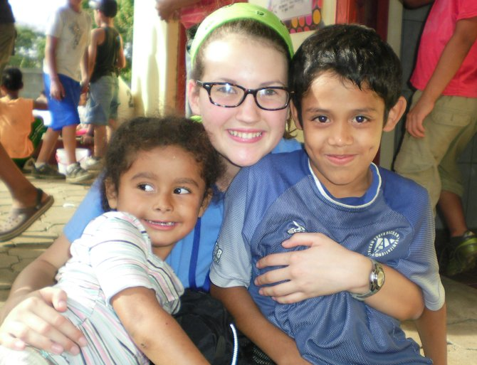 Clare Whitney, a Schroon Lake teen, poses with students from the Chiquilistagua Publico school in Nicaragua. Whitney is planning a 5-kilometer run June 16 to raise lunch money for students at the school.