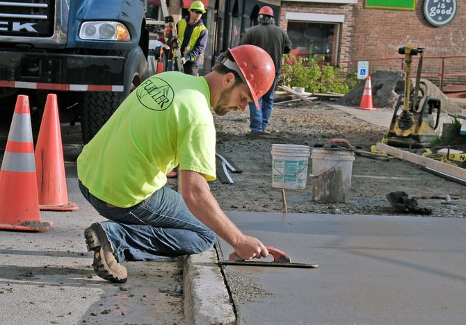 Kyle Parmeter, of Fuller Excavating, smoothes out a fresh pour of concrete on the new Broadway sidewalk adjacent to the Berkeley Green. The village is reconstructing sidewalks along sections of Broadway and Main Street in the downtown business district, and work should be completed by June 15.