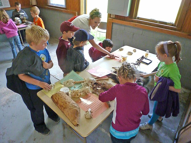 A second grade calls from Pashley Elementary in the Burnt Hills-Ballston Lake Central School District learn about animals living in the Capital Region through a hands-on demonstration at Five Rivers.