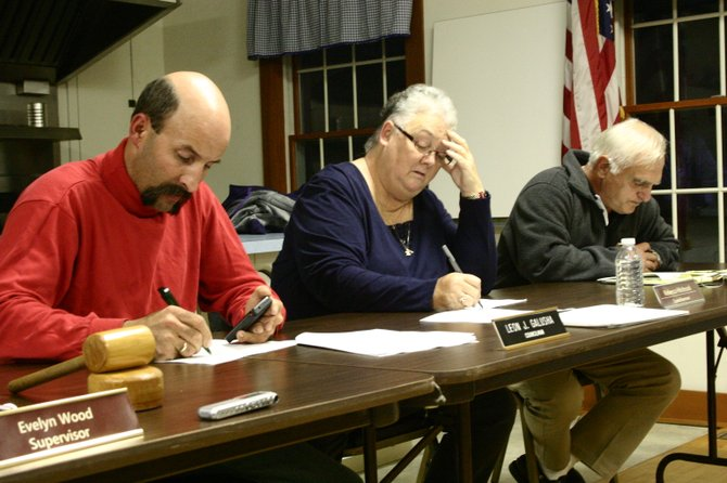 In Oct. 2011, Thurman Town Board members including Becky Hitchcock (center) work on drafting the 2012 town budget after a year of unprecedented financial pressures. Hitchcock, who died May 25, has been credited with bringing a moderate approach and cohesive influence to town politics during challenging times. Hitchcock is flanked by board members Leon Galusha (left) and Al Vasak (right).