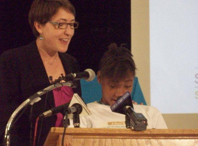 (From left) Kristi Eck, assistant to the operating director and higher education program specialist at Syracuse Say Yes, introduces Yannis Gilbert, a student at Bellevue elementary school, to discuss the book she helped write through Say Yes' Young Authors Series.