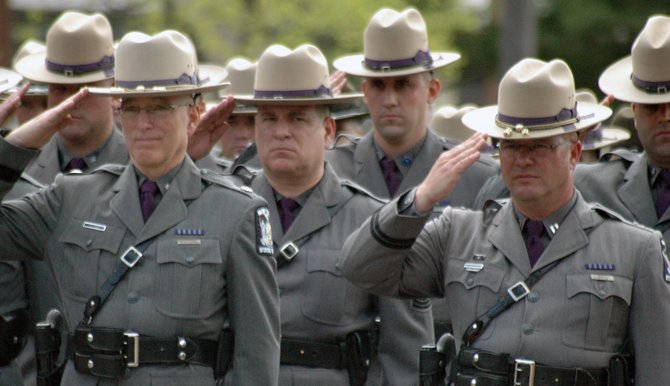 Members of Troop B of the New York State Police salute during the playing of Taps at Memorial Day services May 23.