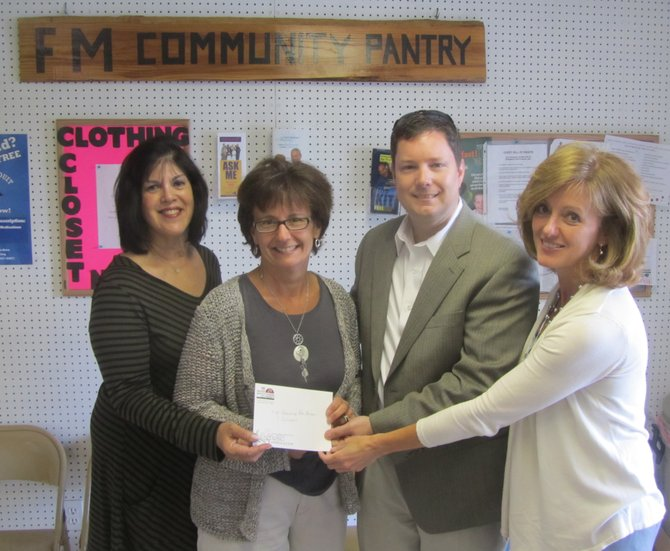 Chamber Vice President Kim Kutzer (far right), President Tim Buckles and board member Cheryl Schotz (far left) present F-M Community Outreach Director Linda Napier with a check for $3,165.