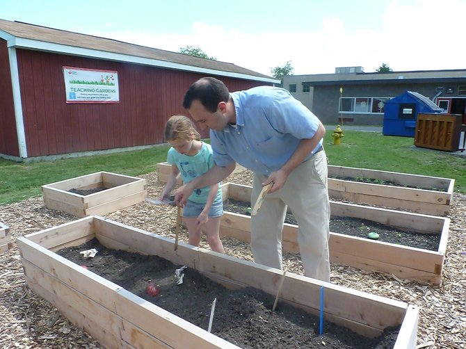 Glenmont Elementary students help plant fruits and veggies in their new Teaching Garden on campus.