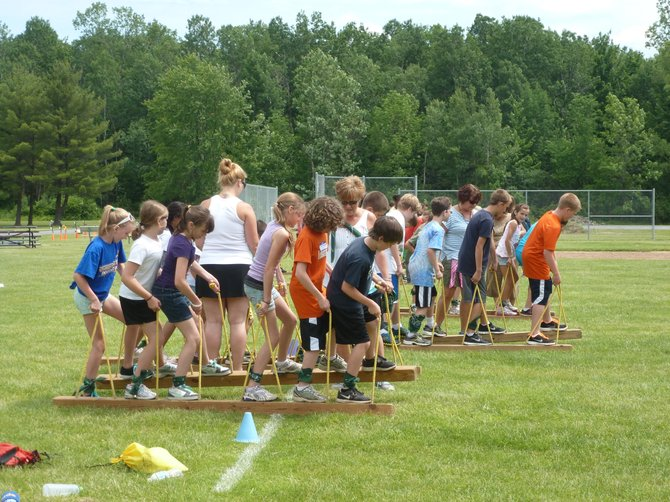 "Bethlehem fifth-graders took part in team-building exercises like the ""trolley,"" in which they walked on wooden planks and learned to tie-dye T-shirts at the annual Survivor Day at Elm Avenue Park on Friday, June 1."