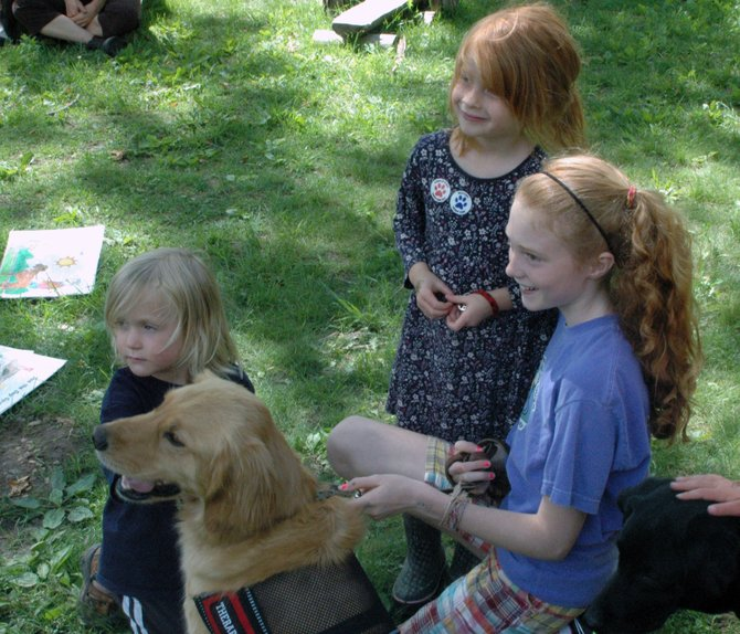 Westport sixth-grader Ellie Storey handles therapy dog Jessie as students from Lakeside School meet them.