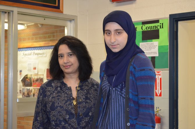 Brown School Writing Center instructor Annu Subramanian, left, stands with eighth-grader Zaina Siraj, who is working on a book for young Muslim girls.