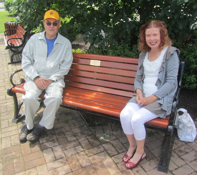 Incoming Manlius Lions Club President Fred Gilbert and Kitty Barrett sit on the bench that was dedicated to the memory of Kitty's late husband, John.