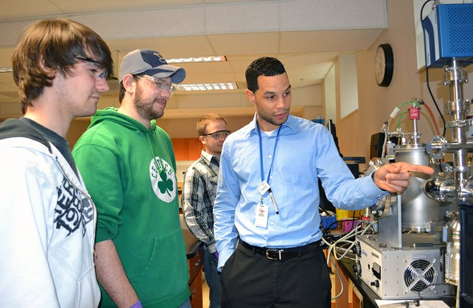 SCCC adjunct professor Simon Miner points out part of a sputtering training system to students, from left, Andrew Doucet, Ed Springli and Apollo Marmarinos in the Nanoscale Materials Technology lab.