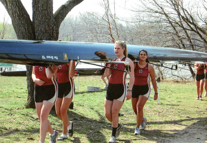 Ellen Burr, center, helps her Boston College teammates carry their racing shell to the water in preparation for a recent race on the Charles River. A standout athlete while attending Cazenovia High School, Burr joined the BC rowing team and experienced much success in her freshman year.