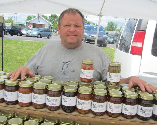 Jim Lowry, of Raindrop Farms in Georgetown, looks over a full rack of preserves. He's continuing a family tradition of selling locally grown produce at the Manlius Farmer's Market.