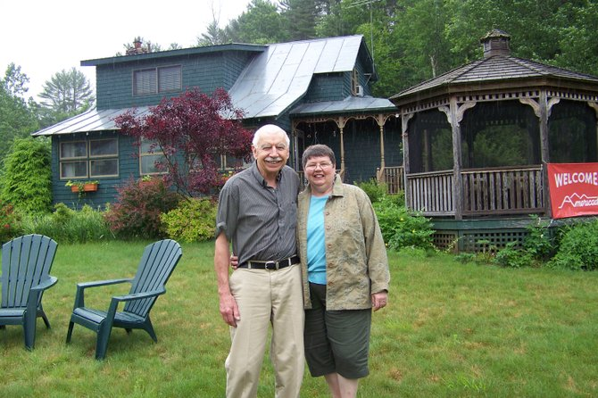 Steve and Sandi Parisi stand in front of their enterprise, Country Road Lodge Bed & Breakfast, which has won awards for its rustic riverside ambiance and gracious hospitality. Steve and Sandi have decided to retire and close down Country Road Lodge, believed to be the longest-running single-owner bed and breakfast enterprise in the nation. June 10 was its last day in operation.