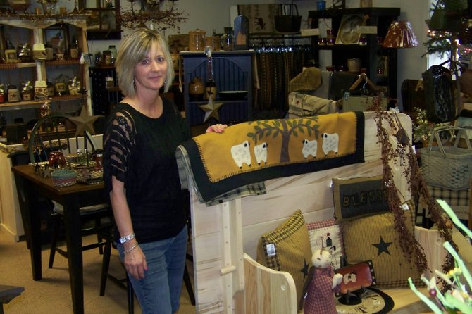 Rebecca Witz Swan poses amongst the extensive display of home furnishings at her Warrensburg enterprise, Rebecca's Florist & Country Store, which was recently awarded as  'Business of the Year' by the Warrensburg Chamber of Commerce. Swan launched the store two years ago, and it has achieved considerable success in an uncertain economy and a highly competitive local commercial scene.