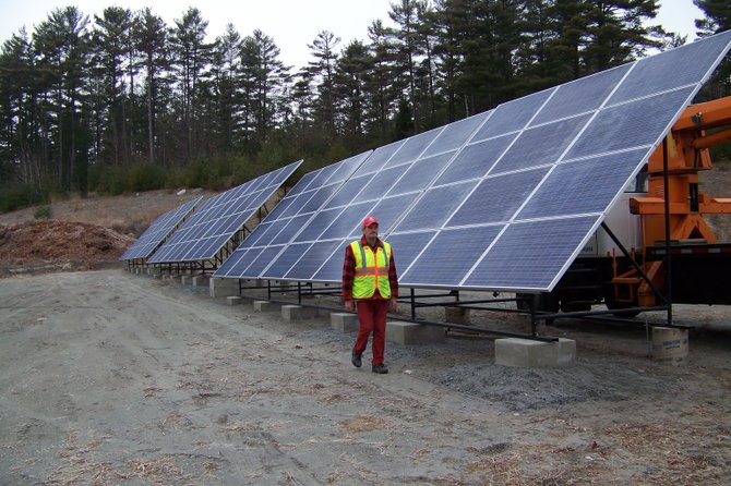 Town of Chester landfill and recycling attendant Lou Lashomb walks past an array of solar panels, one of two installations 150 feet long, that will soon power the town transfer station, town garage complex, and  Chester recycling center. The town of Chester decided this week to double the number of arrays and the electrical output of their solar installations to both save money and become more earth-friendly. The town is now converting to solar power to provide electricity for all their facilities, including the Chester-Horicon Health Center, the town highway garage, the Chester Municipal Center, and the Dynamite Hill complex. Area energy officials say Chester is leading the way in employing such alternative energy sources.