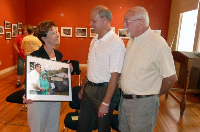 New York State Assemblywoman Teresa Sayward displays a picture from the Ragin River exhibit to Jay Supervisor Randy Douglas and Keene Supervisor William Ferebee.