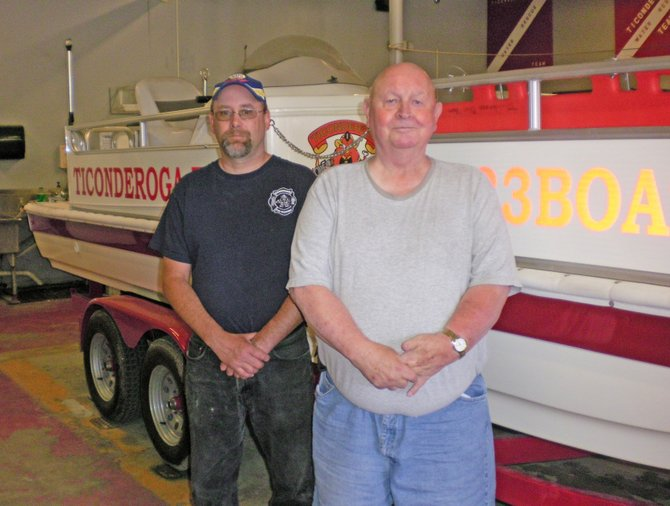 Ticonderoga Fire Department Chief Jeff Burns and Commissioner Calvin Cross stand with the company's new rescue boat. The craft was donated by Snug Harbor Marina.