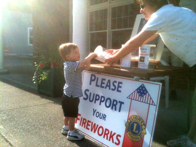 Cazenovia Lions Club member Sandy LeVan, right, helps resident Sam Kagey reach the fireworks fund collection can, as he donates his weekly allowance on June 16. The Lions Club is only about $3,000 away from its goal of $10,000.