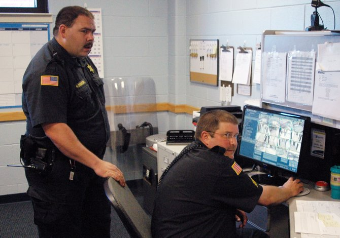 Officers Nicholas Denton and Pete Feeley watch tape to make sure nothing inappropriate was happening.