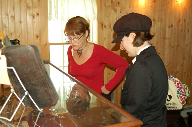 "Sharalee Falzerano, left, gives a tour of ""The Country Doctor"" exhibit at the Owens House in North Creek. News Enterprise Reporter McKenna Kelly, right, listens to stories about the various physician instruments on display."