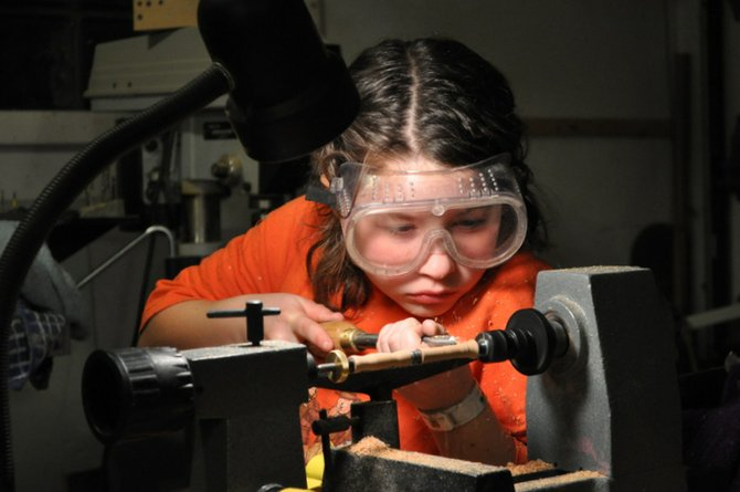 Anna Williams, an 11-year-old of Glenville, turns wood on a lathe to finely carve out one of her handmade pens. Williams' handmade pen hobby ended up turning into a profitable business.