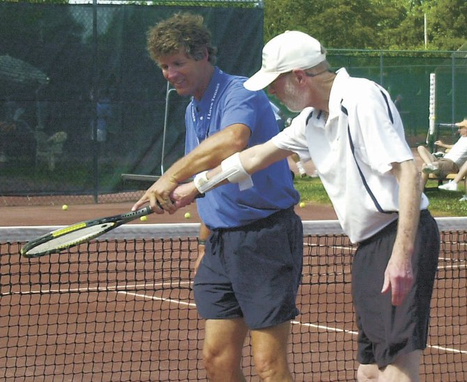 Albany Tennis Center manager Larry Yakubowski, left, shows John Tomer proper form on a backhand shot Saturday morning at Ridgefield Park. The Delmar resident runs a facility that features the only clay courts in the Capital District.