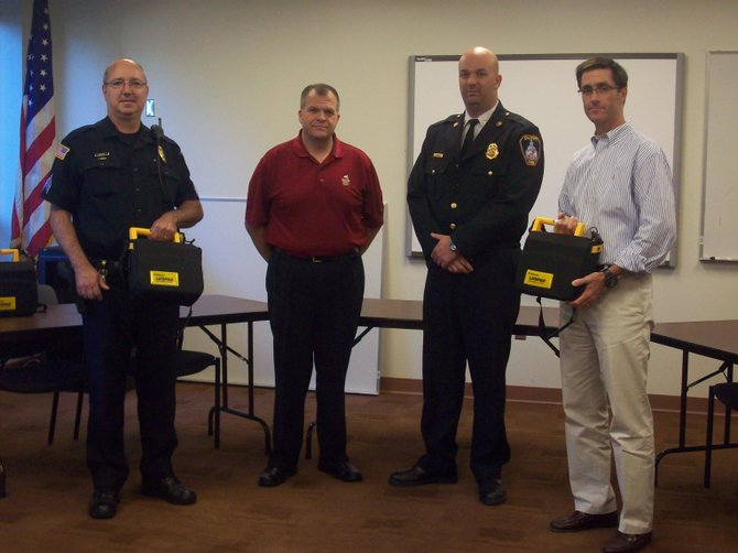 (From left) DeWitt Police Sargent John Mossotti, towns board councilor Brian Schultz, fire department Chief Jason Green and JDYAA board president Eric Johnson pose with the AEDs donated to JDYAA and the DeWitt Police Department.
